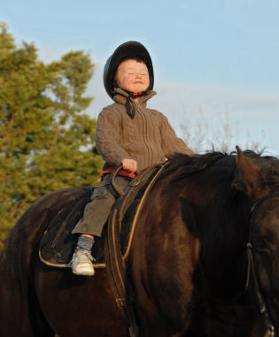 little boy and her black stallion happy... focus on the head of child